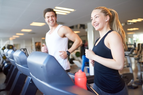 Man and woman laughing on a treadmill