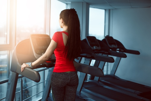 Female standing on a treadmill in a gym