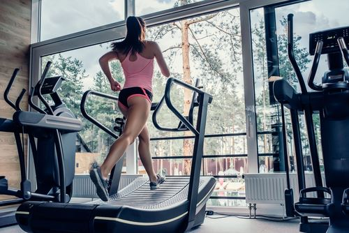 Woman running on a curved treadmill